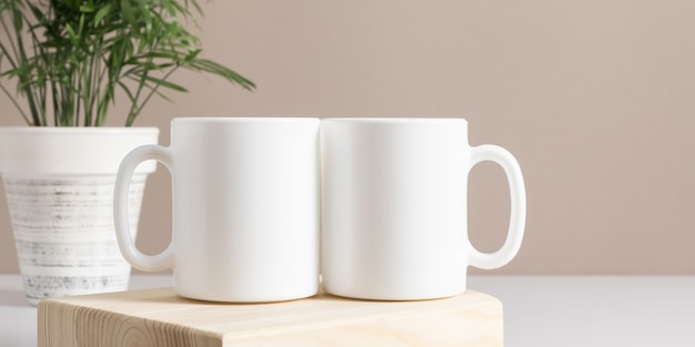 Two mugs mockup on beige table front view