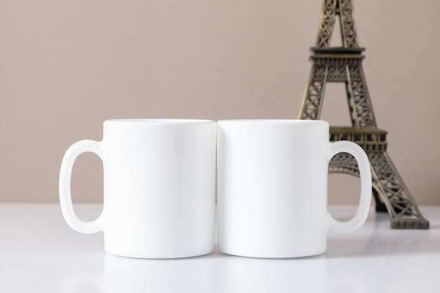 Two mugs mockup and layout of eiffel tower on table front view