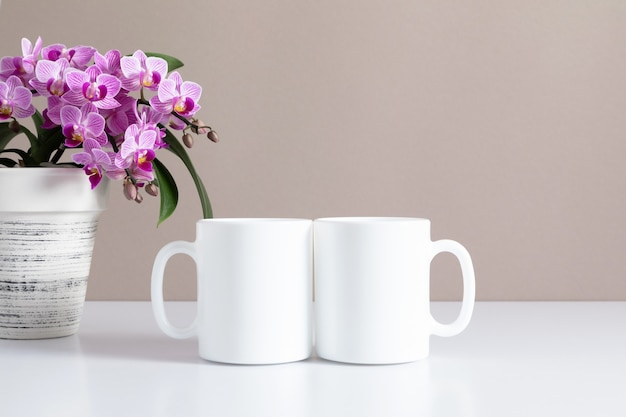 Two mugs mockup and pink orchid flower on table front view