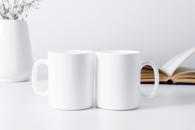 Two mugs mockup with a book and flowers in a vase on a white table