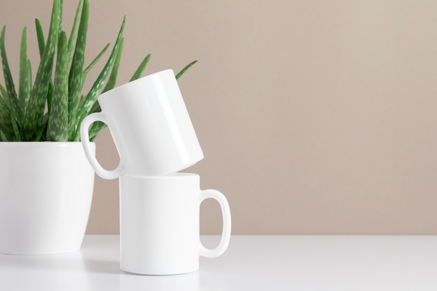 Two mugs mockup with green plant front view