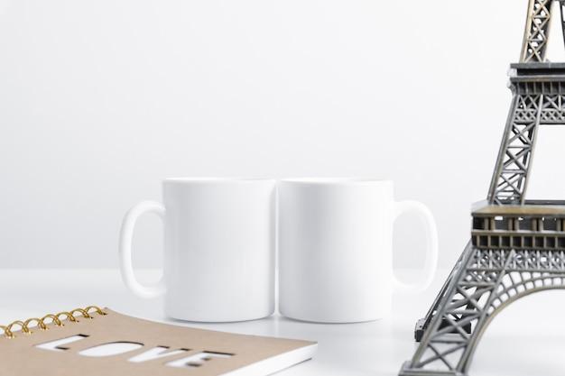 흰색 테이블에 작업 공간 액세서리와 함께 두 개의 머그컵 모형
