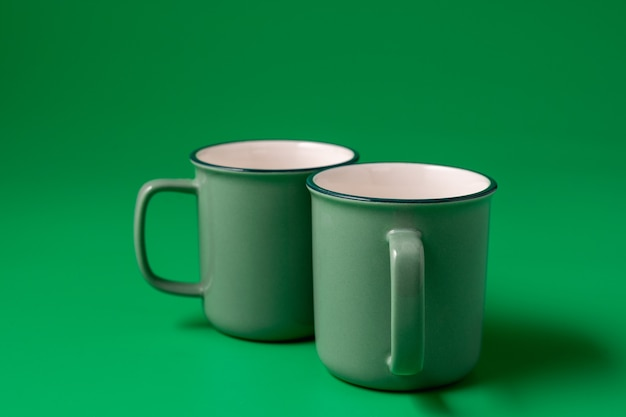 Two mugs of neo mint color on green
