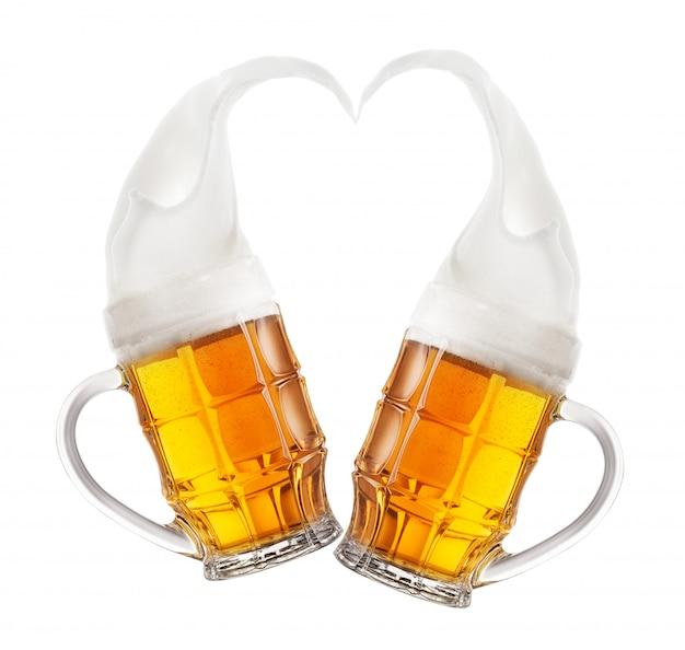 ハートの形の泡の飛沫とビールの2つのマグカップ