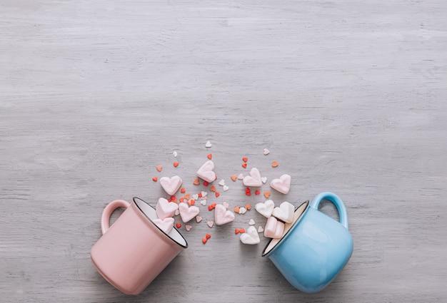 青とピンクの2つのマグカップが横になり、小さなキャンディーハートとマシュマロハートがこぼれました