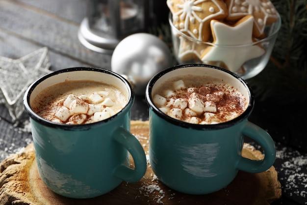 Две кружки горячего какао с зефиром и печеньем на черном столе