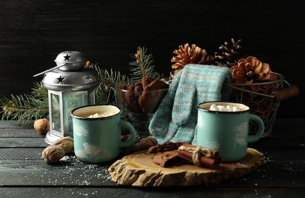 Две кружки горячего какао с зефиром и перчатками на черном столе