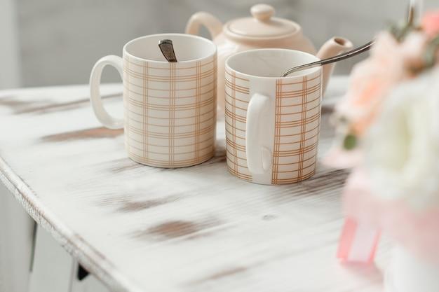明るい背景の白いテーブルにアクセサリーと花と2つのマグカップ。ティースプーン付きマグカップ。
