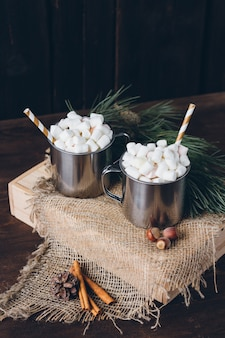Two mugs with cocoa and marshmallows on a brown background