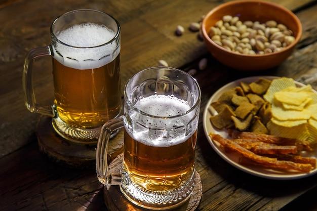 거품 맥주와 피스타치오가 든 머그 2개와 칩이 나무 테이블에 올려져 있습니다.