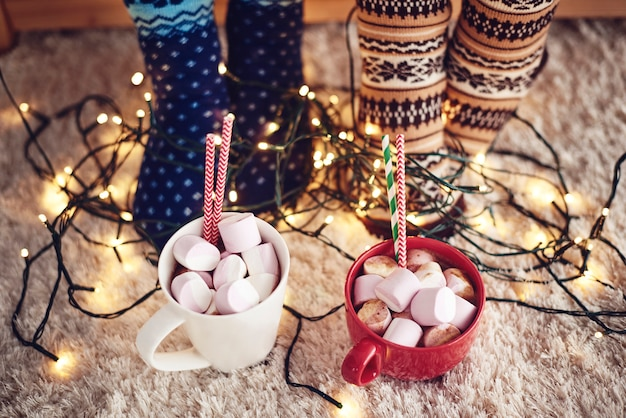 Two mugs with hot chocolate and marshmallow on rug