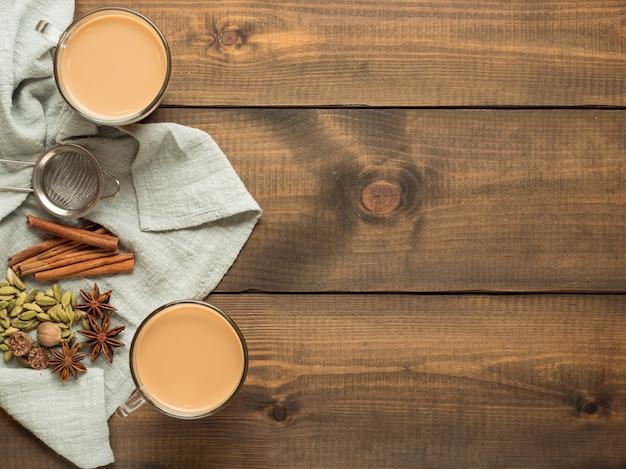 Две кружки с чаем масала стоят на деревянном столе со специями. вид сверху.