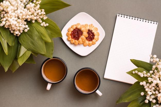 緑のテーブルにお茶、クッキー、ノート、スズランの花束が入った2つのマグカップ。休息、スローライフ、計画、目標設定のために一時停止します。上面図