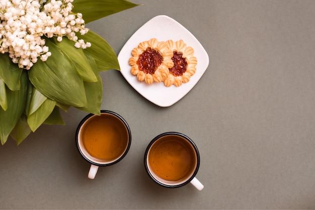 お茶と2つのマグカップ、皿にクッキー、緑のテーブルにスズランの花束。休息のために一時停止し、人生を遅くします。上面図