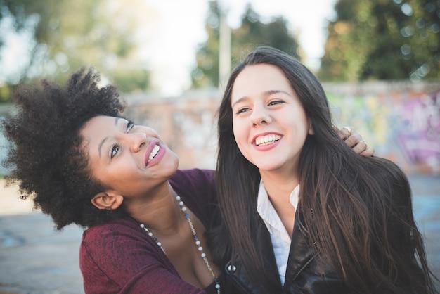 楽しんでいる2人の多民族の美しい若い女性