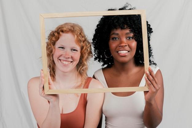 Two multi ethnic female friends looking through one wooden frame against grey backdrop