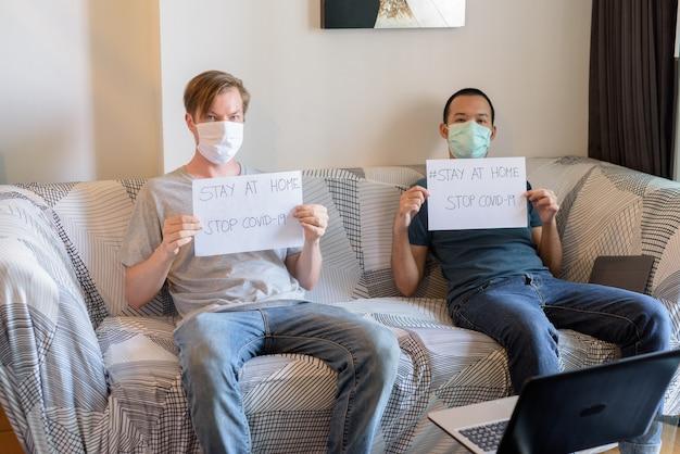 自宅で検疫下にいる間、stay at homeのサインを見せている友人としてのマスクを持つ2人の多民族男性
