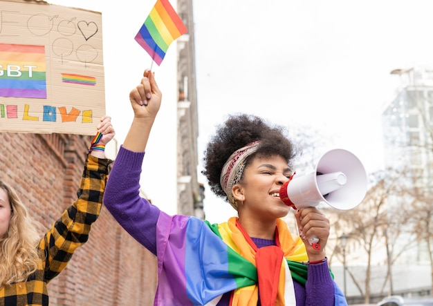 Two multi-ethnic women celebrating gay pride event wearing the rainbow flag symbol of the lgbt social movement