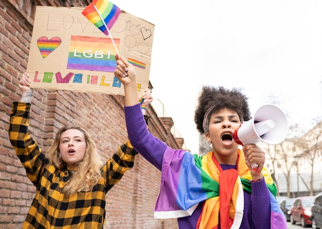 Two multi-ethnic women celebrating gay pride event wearing the rainbow flag symbol of the lgbt