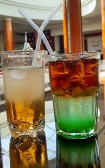 Два разноцветных коктейля с разной начинкой с трубочкой в стеклянных бокалах