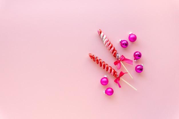Два разноцветных леденца на палочке с шариками на розовом
