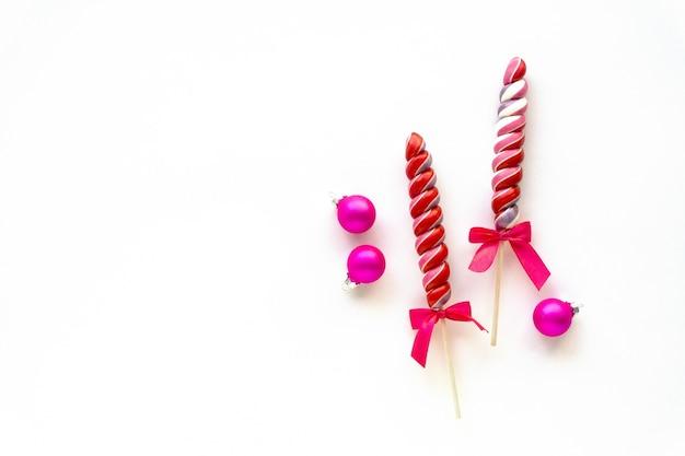 Два разноцветных леденца на палочке с розовыми шариками на белом фоне. место для текста.