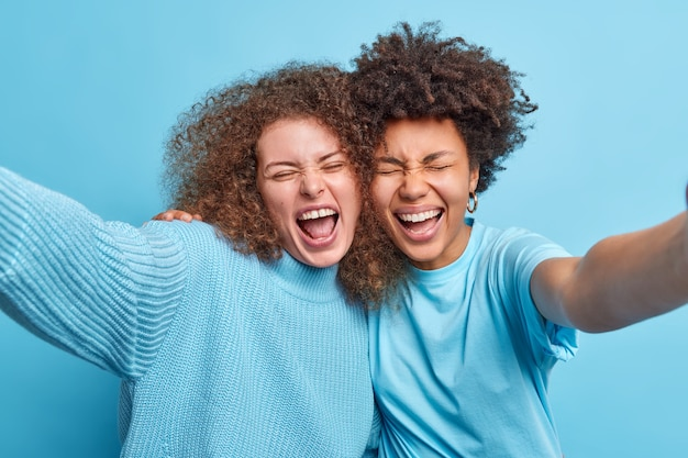 Two multicultural best female friends embrace and have fun while posing for selfie spends free time together dressed in casual clothes isolated over blue wall. international friendship