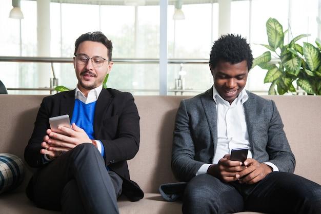 두 명의 다문화 남성이 소파에 앉아 휴대폰을 들고
