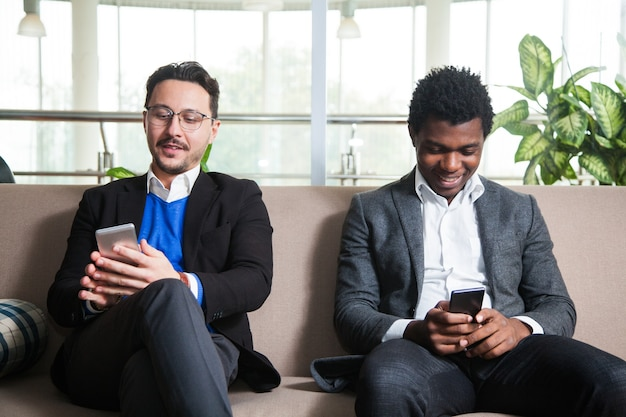 Two multicultural men sit on sofa and hold mobile phones
