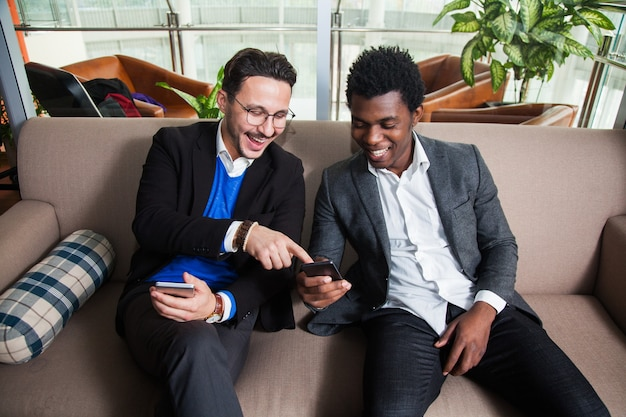 Two multicultural men sit on sofa, smile and hold mobile phones