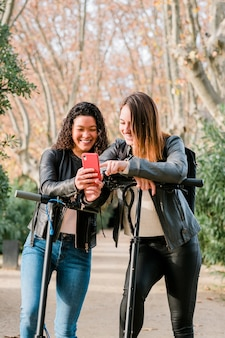 Two multiethnic female friends on electric scooters using smartphone outdoors