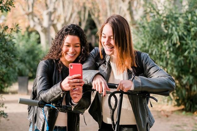 屋外でスマートフォンを使用して電動スクーターで2人の多民族の女性の友人