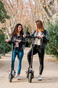 電動スクーターに乗った2人の多民族の女性の友人