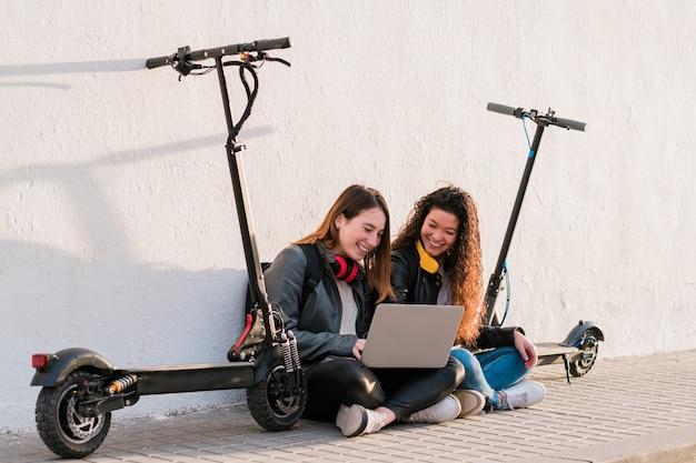 ノートパソコンを使用して電動スクーターで通りのそばに座っている2人の多民族の女性の友人