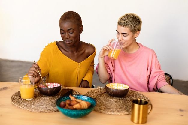 Two multiethnic girlfriends having breakfast together at home