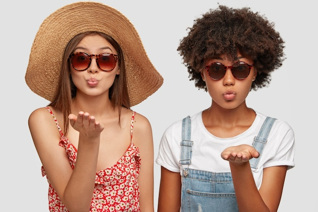 Two multiethnic sisters blow airkiss at camera, wears trendy shades, summer clothing