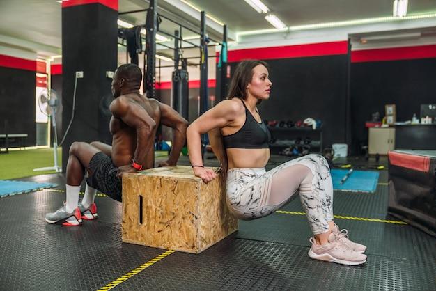 ジムの木製の箱で上腕三頭筋の調子を整えるエクササイズをしている2人の多民族のボディービルダーアスリート。クロスフィットトレーニングルーチンを行うアフリカのボディービルダーと白人のボディービルダー