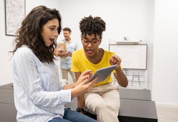태블릿으로 일하는 두 명의 다인종 여성