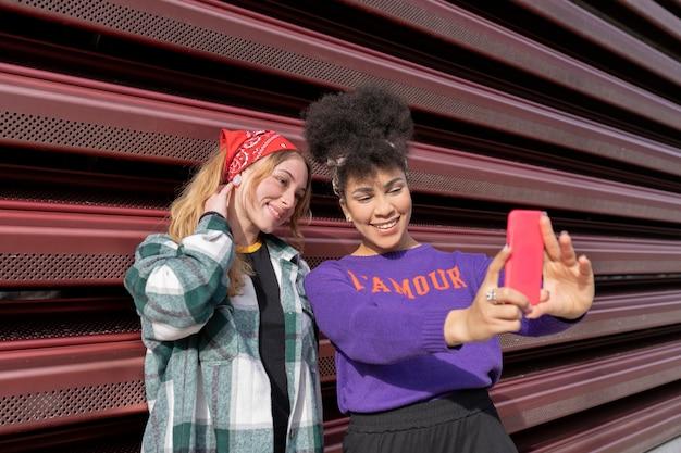 Two multiracial women taking selfie in the street
