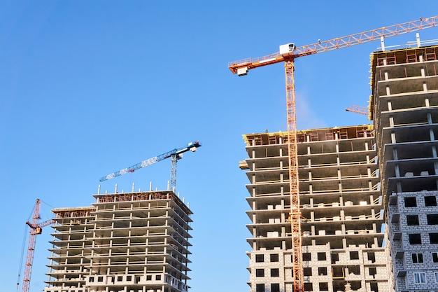하늘을 배경으로 타워 크레인으로 건설 중인 두 개의 다층 아파트