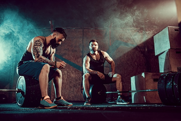 Two muscular bearded tattoed athletes training at gym
