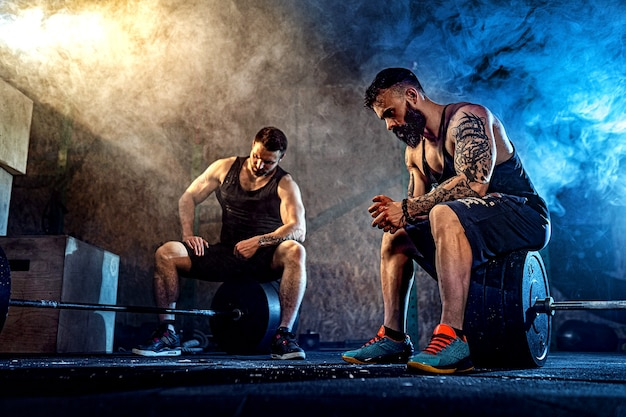 Два мускулистых бородатых татуированных спортсмена расслабляются после тренировки, поднимая тяжелый вес. курить в спортзале