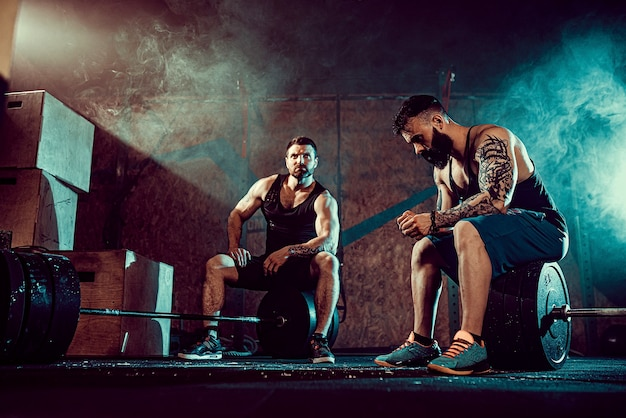 Два мускулистых бородатых татуированных спортсмена расслабляются после тренировки, поднимая тяжелый вес