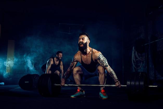 Два мускулистых татуированных спортсмена с бородой тренируются, один поднимает штангу с тяжелым весом, когда другой мотивирует