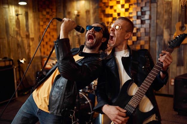 マイクに向かっている2人のミュージシャン、ステージで演奏する音楽。ロックバンドの演奏またはガレージでの繰り返し、楽器を持った男、ライブサウンドパフォーマー