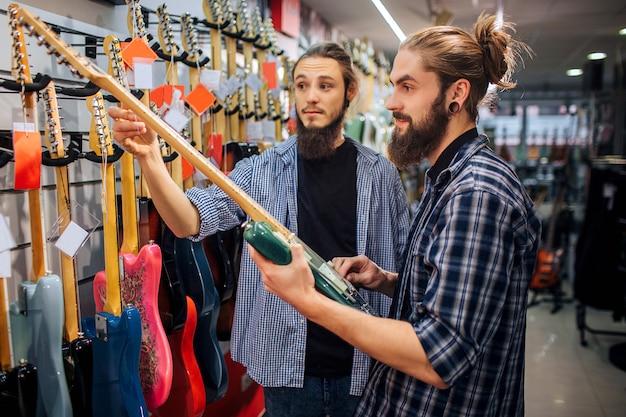 Два музыканта стоят вместе на гитарном ряду. один молодой человек держит гитару белого цвета, другой касается ее бара. они в гитарном магазине.