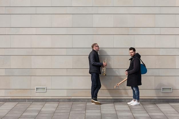 壁の前に立つ2人のミュージシャン