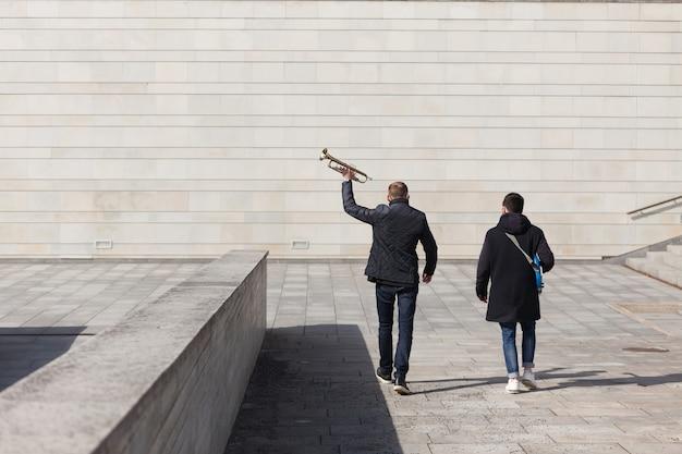 コンクリート環境下を歩く2人のミュージシャン