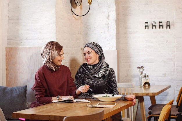 Two muslim business ladies met in a cafe and discuss working moments writing everything in a notebook