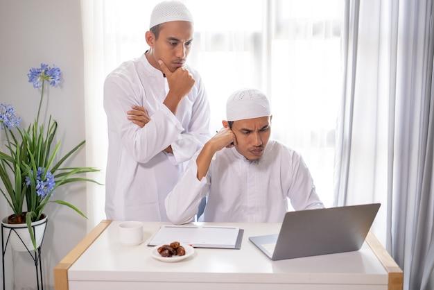 一緒にラップトップを使用して話し合い、会議する2人のイスラム教徒のビジネスパートナー